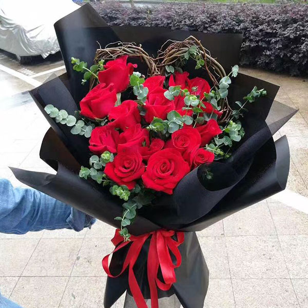 Medium bouquet of 19 red roses that features a heart-shaped wreath wrapped in matte paper