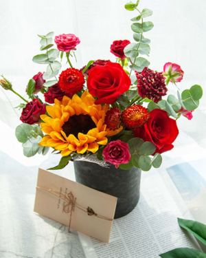 Medium assortment of sunflower, roses, lisianthus, and eucalyptus arranged in a cylinder gift box
