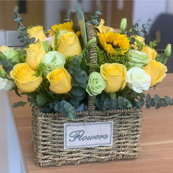 Medium assortment of sunflowers, roses, lisianthus and mixed foliage arranged in a classic hanging basket