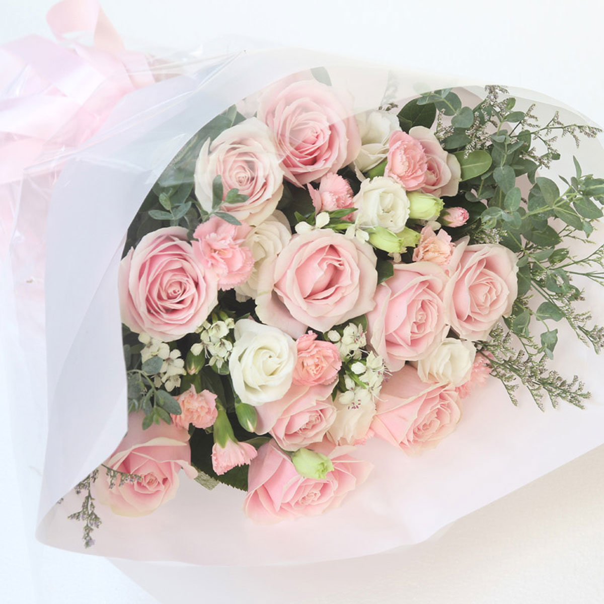 Medium bouquet of pink roses, carnations, eustomas and greenery wrapped in quality matte paper