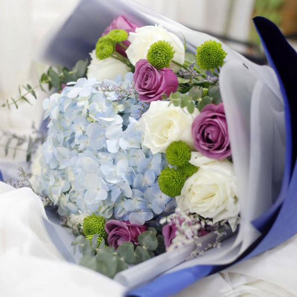 Medium bouquet of blue hydrangeas with purple and white rose accents wrapped in quality matte paper