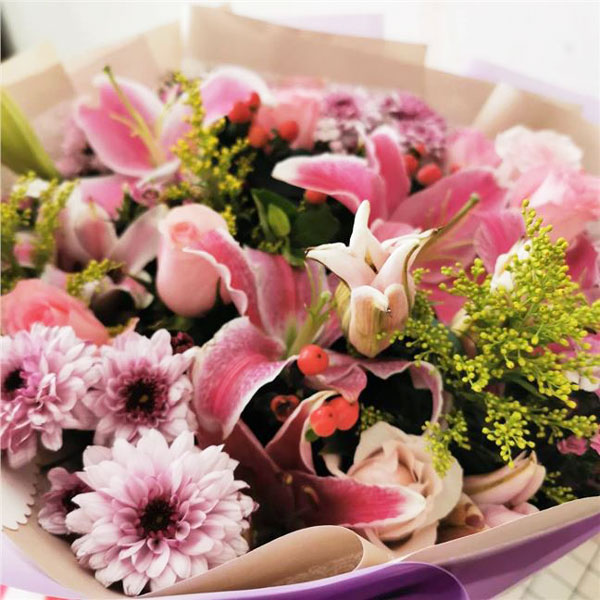 Medium bouquet of pink roses, oriental lilies, chrysanthemums and foliage accents wrapped in quality matte paper