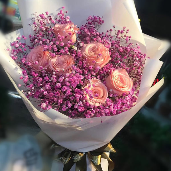 Medium bouquet of 6 pink roses and baby's breath flowers wrapped in quality matte paper