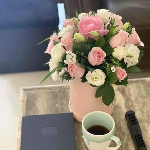 Medium assortment of pink roses, eustomas, jasmine petals, and foliage arranged in a cylinder gift box