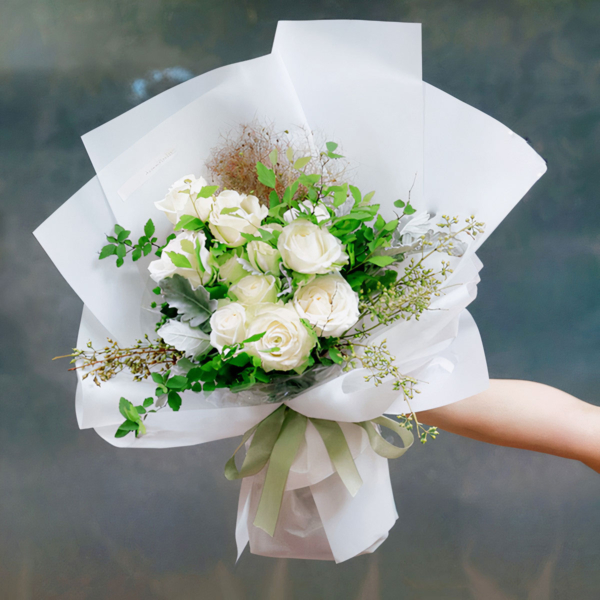 Medium bouquet of 9 white roses and seasonal green flowers wrapped in quality matte paper