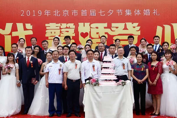 Many brides and grooms stand in front of a red drop to get married together on Chinese Valentines Day